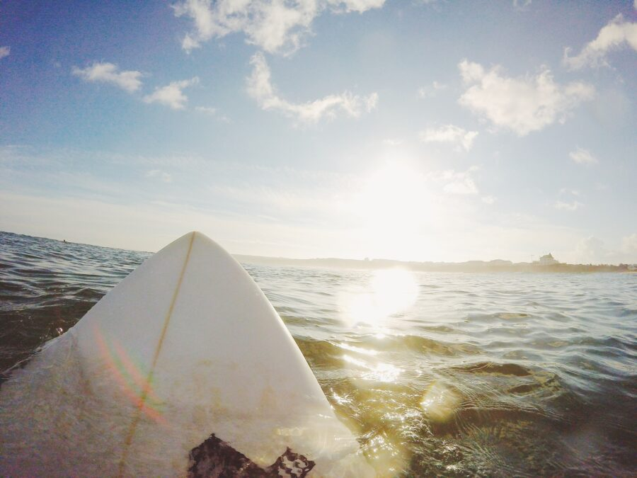 A POV of a white surfboard out in the water late in the aternoon - what you'll see while surfing Lagos Portugal