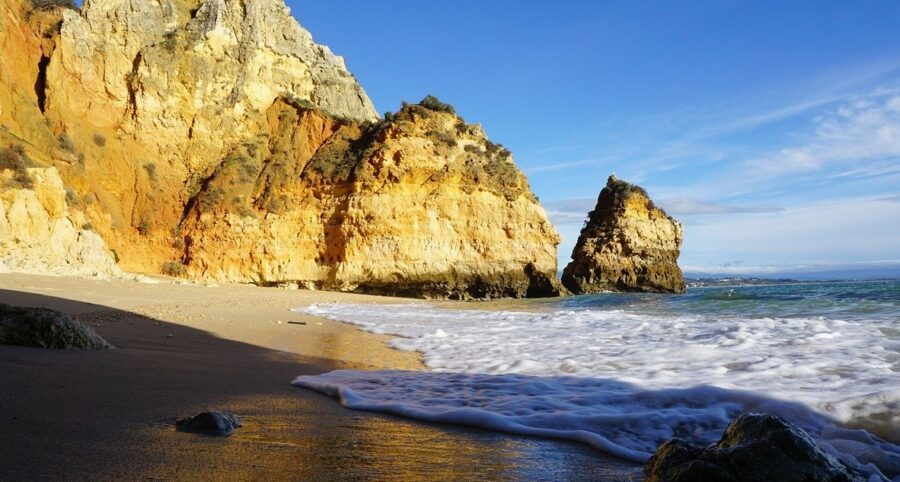A pristine beach, flat except for a couple of rocks, with views of towering cliffs nearby, in the Algarve region of Portugal