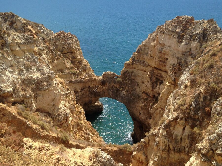 A stone arch surrounded by sandstone cliffs at Ponta da Piedade, one of the best places to visit in Lagos