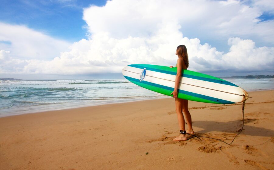 A woman holding a green, blue, and white surf board on the shore, looking at the waves in the distance, while surfing in Lagos Portugal