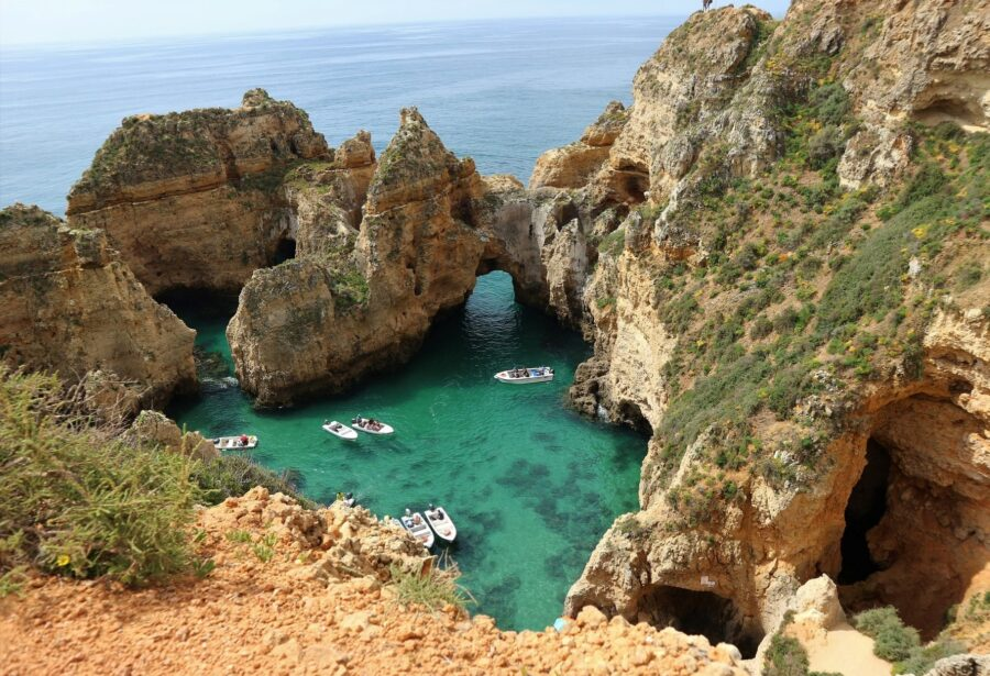 7 white boats touring the green-blue waters of a bay at Ponta da Piedade, one of the best beaches of Lagos Portugal