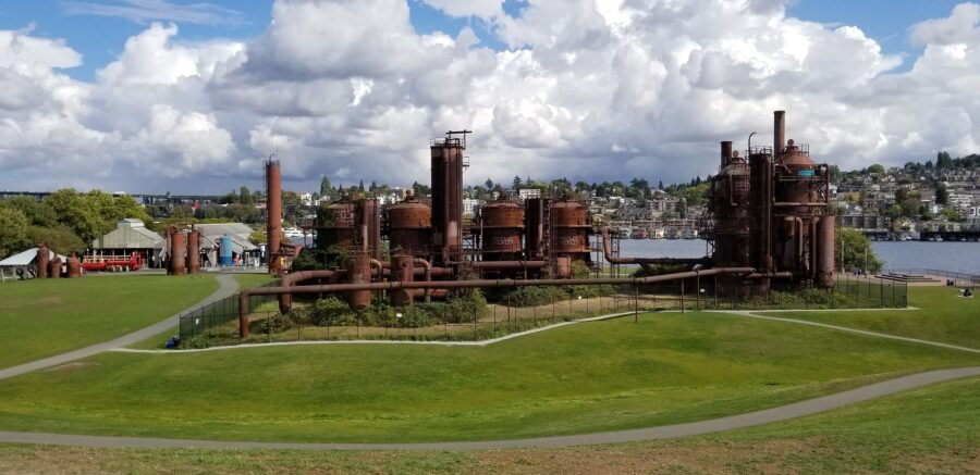 The Seattle walking trails at Gas Works Park, with views of a green field, Pacific Ocean, and distant Seattle suburbs