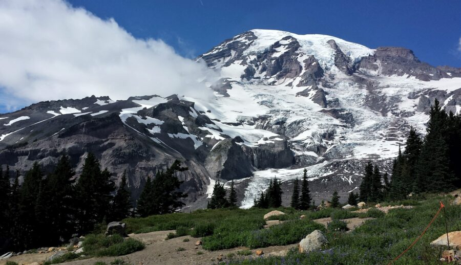 View of Mount Rainier off a trail in the summer, with some clouds in the middle and dark trees in the foreground - one of the best day trips in Seattle