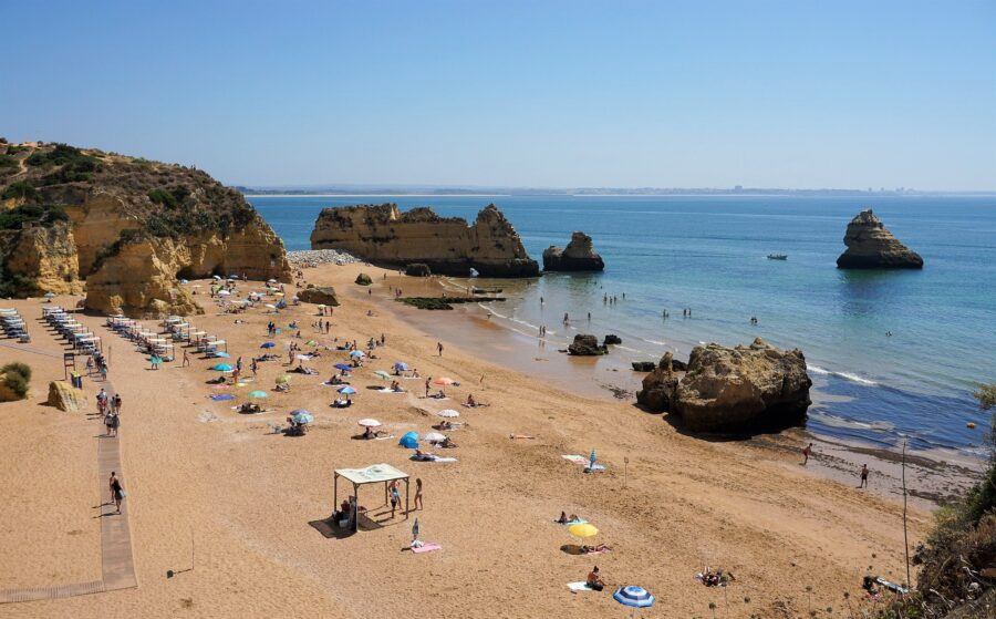 A small crowd of tourists and locals enjoying the sandy beach and blue water at the Praia Dona Ana in Lagos, Portugal