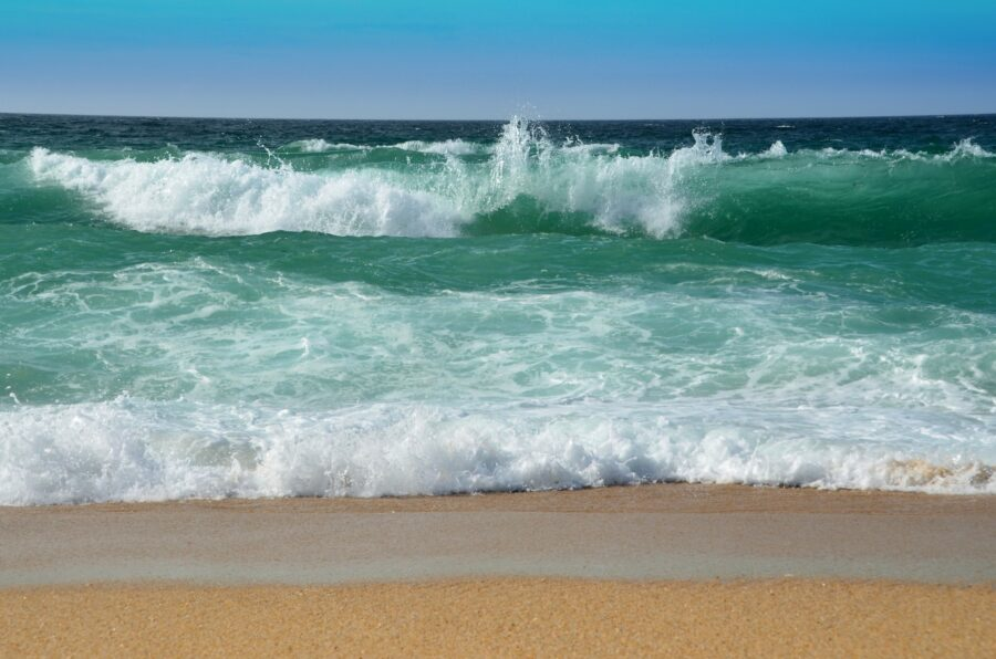 Sizable waves in the blue-green water at Praia do Canavial, one of the beaches of Lagos Portugal!