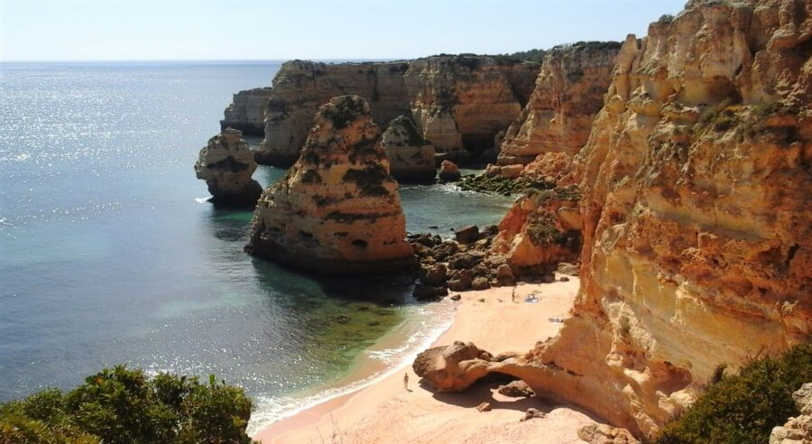 The Praia do Barranco do Martinho at low tide, surrounded by towering ochre cliffs - one of the wonderful beaches of Lagos Portugal