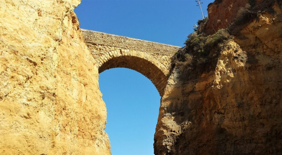 The tanned, stoned Roman bridge, once part of the Pinhão Fortress, at Praia dos Estudantes, one of the best beaches of Lagos Portugal