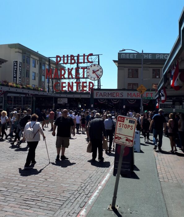 Large crowds in front of the Public Market Center sign at Pike Place in July, one of the best times to visit Seattle