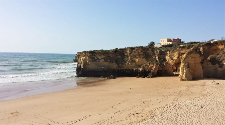 The empty Praia da Batata Lagos Portugal beach on a sunny day, covered in flat amber sands and views of ochre cliffs