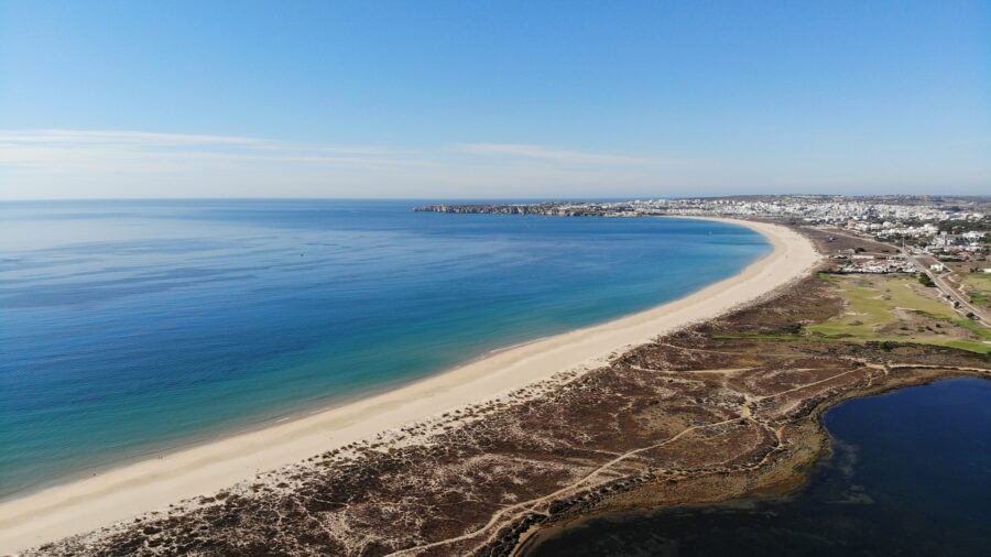 The long and thin stretch of sand that makes up Meia Praia Beach in Lagos, Portugal, with the deep blue ocean and Lagos seen at a distance