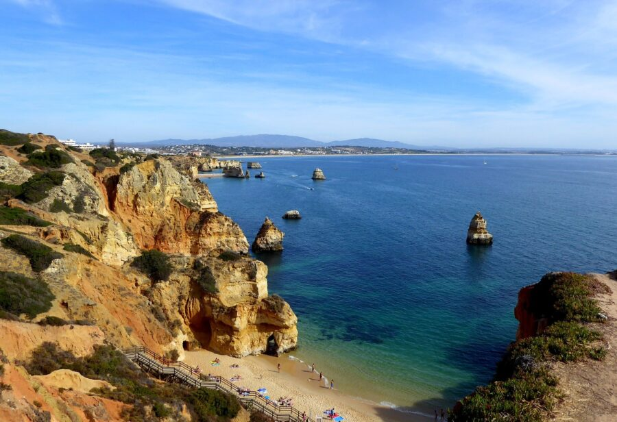 Viewpoint of the tanned cliffs and blue ocean of the Lagos Portugal coastline and Praia do Camilo from on top of a cliff