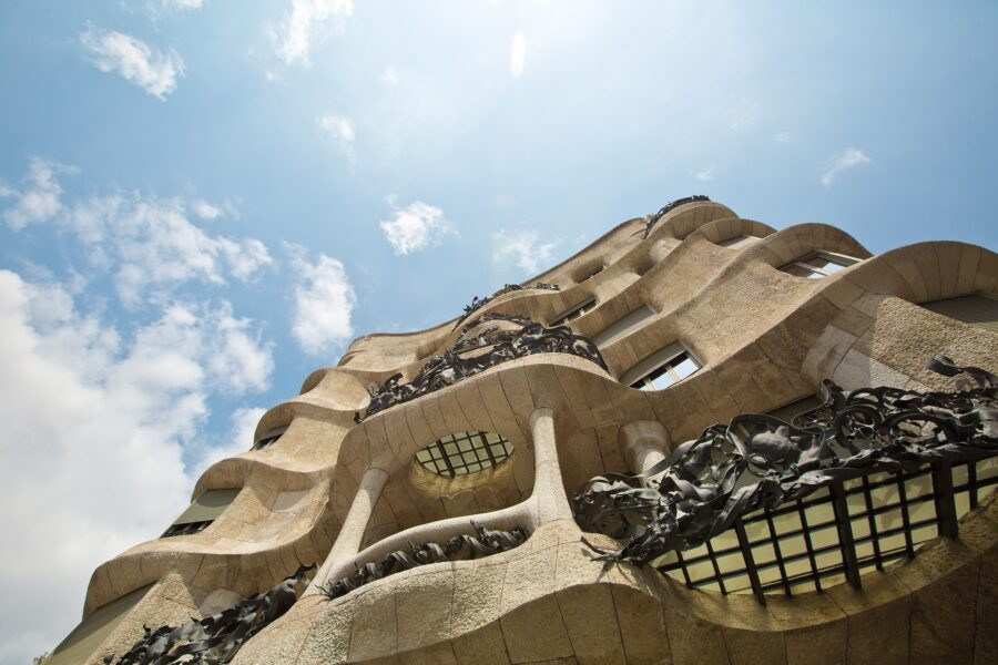 A photo looking up at the tanned Casa Mila on a sunny day with few clouds in the sky, a stop on my itinerary for Barcelona