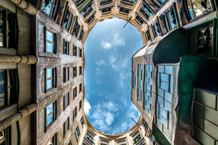 A slightly darkened photo looking up at the blue sky from the ground level of the Casa Mila Barcelona