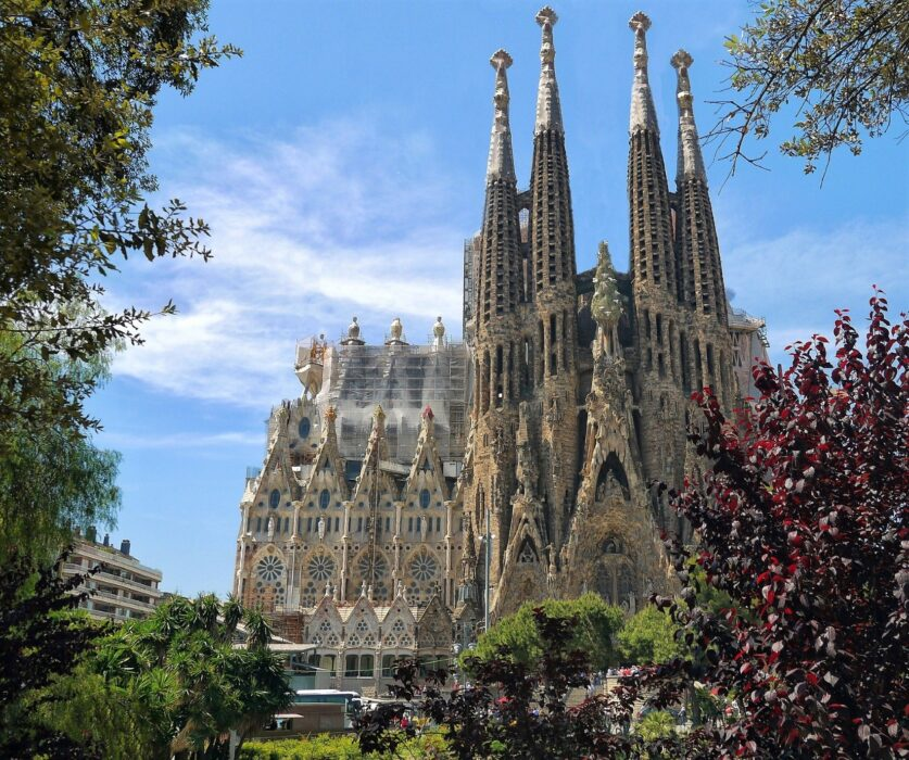 A view of the front of La Sagrada Familia from across the street on a sunny day, framed by trees and shrubbery in Barcelona, Spain