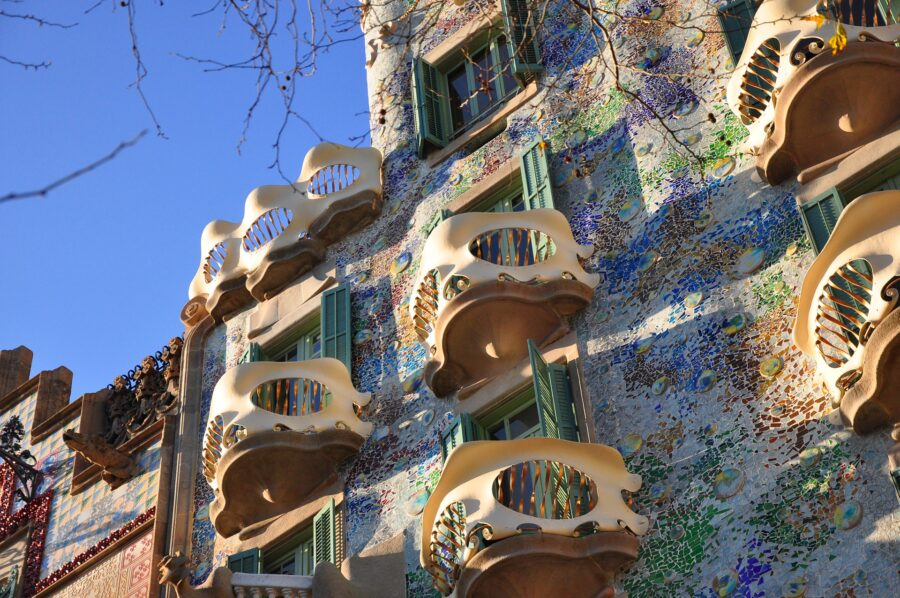 A view of the exterior green, tanned, blue, and white Casa Battlo with its curvy decks in Barcelona