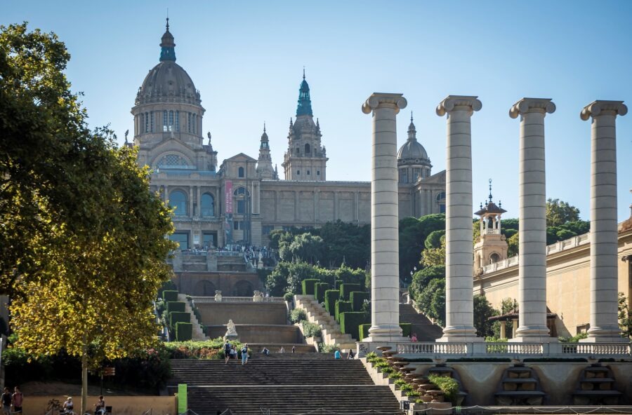 The stairs, four white pillars, and front of the MNAC in Barcelona Spain, with a third of the MNAC covered by trees  - One of the best things to do with kids in Barcelona!