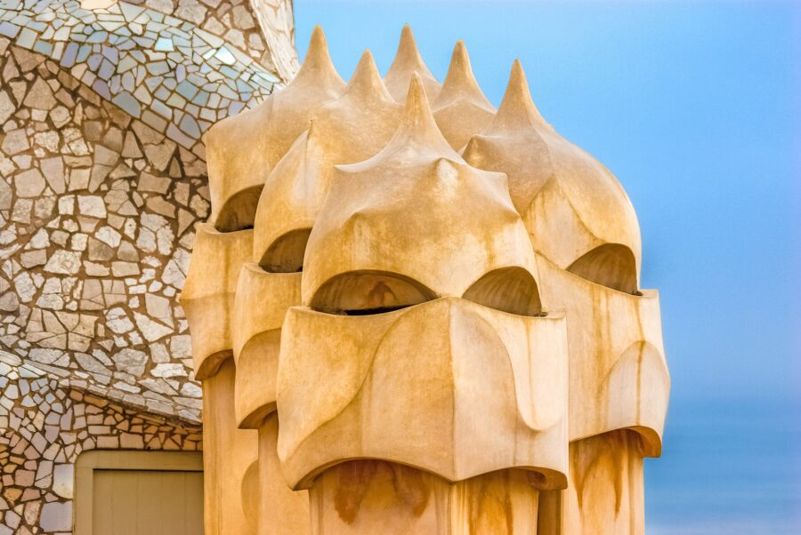 A few wooden statues on top of the roof at the Casa Mila in Barcelona on a sunny day