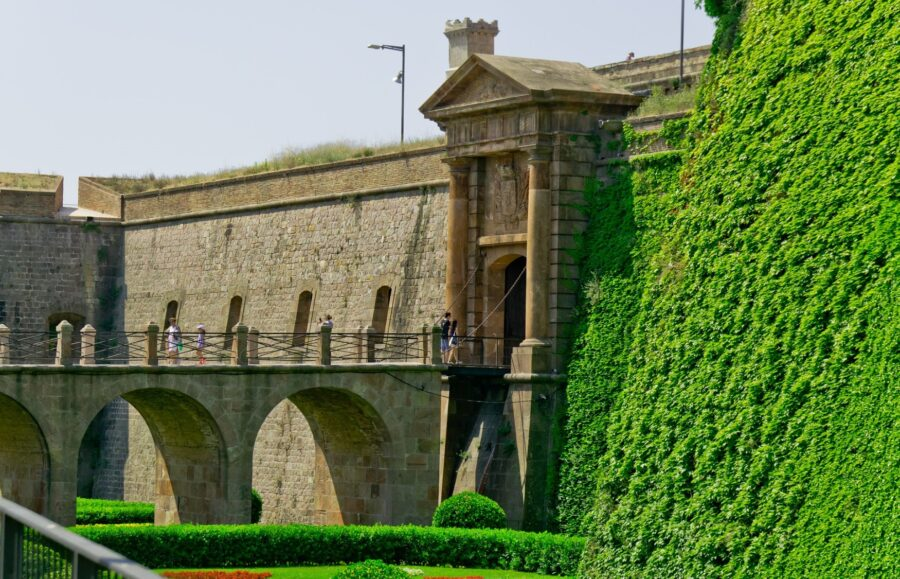 The side view of Montjuic Castle - perfect for your 2 day Barcelona itinerary - with half the castle covered in green shrubbery and vines and the other side bare, and a few tourists crossing a small bridge towards the entryway