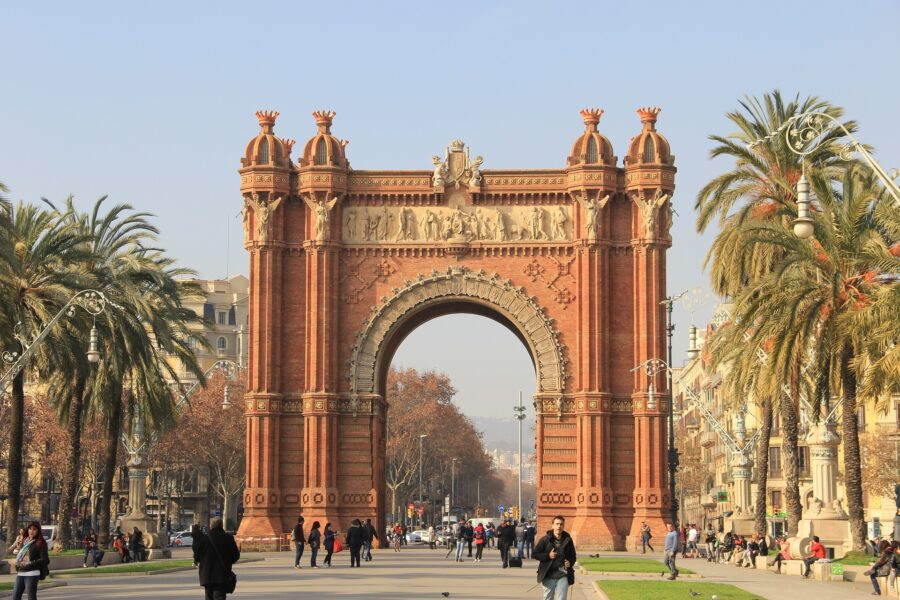 The orange and tan Arc de Triomf at the edge of the Parc de la Ciutadella, surrounded by palm trees on a hazy sunny day - one of the best free things to do in Barcelona