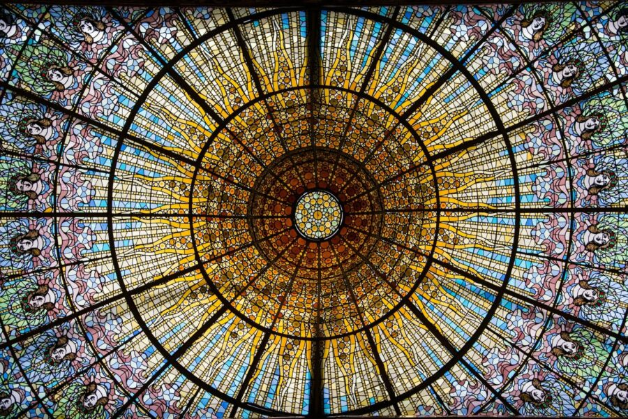 The colorful red, green, blue, yellow, and orage glass window of the ceiling of the Barcelona Cathedral, one of the best things to do in Barcelona when it rains