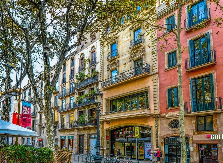 The colorful pink, yellow, and tan buildings in the shopping districts in Barcelona Spain, with its balconies covered in plants