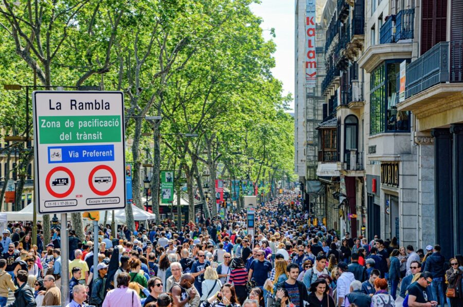 """The streets of La Rambla filled to the brim with tourists, with a sign stating """"La Rambla"""" and the green trees bright in the sun"""