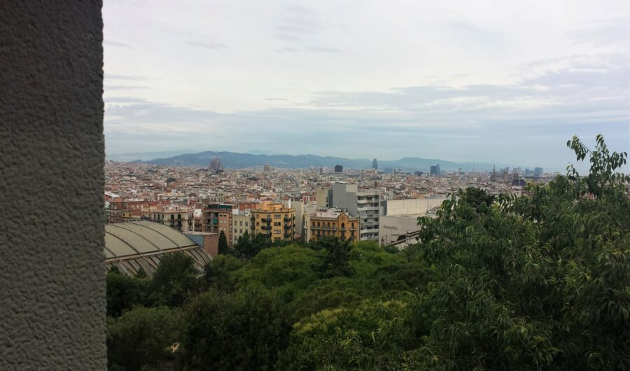 The view from the top of Montjuic in Barcelona on a dark, slightly overcast day, featuring distant buildings showcasing the Barcelona architecture and green trees.