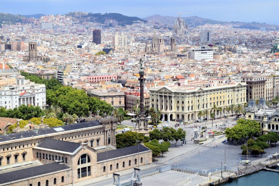 The view of Barcelona from the waterfront from above, including La Sagrada Familia and the Barcelona Cathedral, on a hazy but sunny day